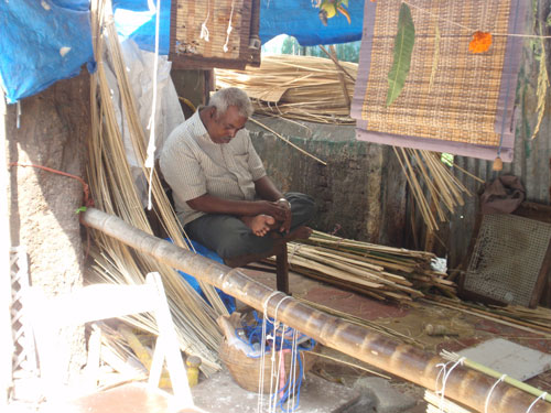 A artisan making blinds on the footpath