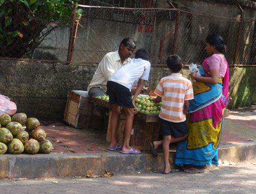 Many vendors sell fruits and vegetables from small stalls on the footpath