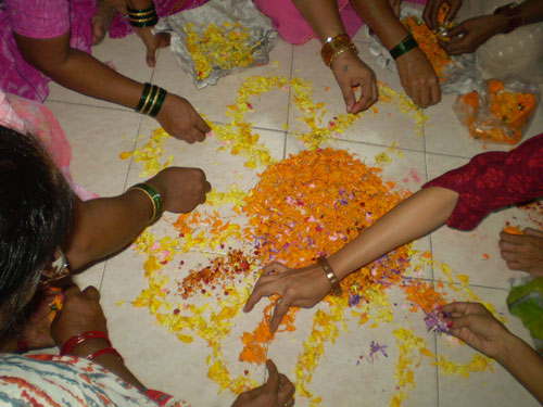 The pattern is emerging – the women had wanted powders too, but made do with petals.  I love this photographs with all the hands of the women all doing something to make a collective artwork – I do consider Rangolis as a work of art as women do it completely free-hand.